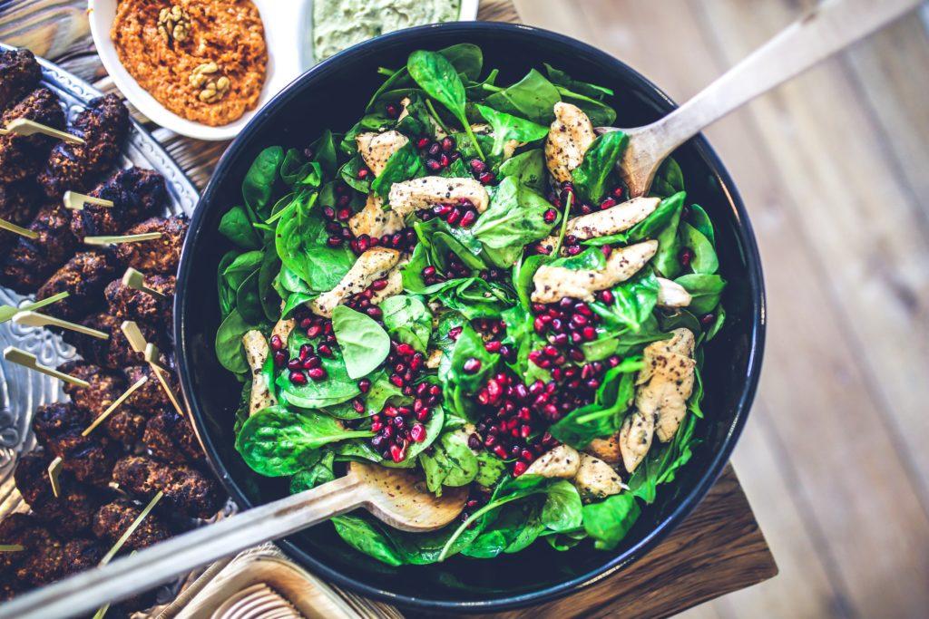 Chicken spinach salad in black bowl