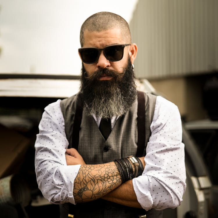 Man with shaved head and beard wearing sunglasses