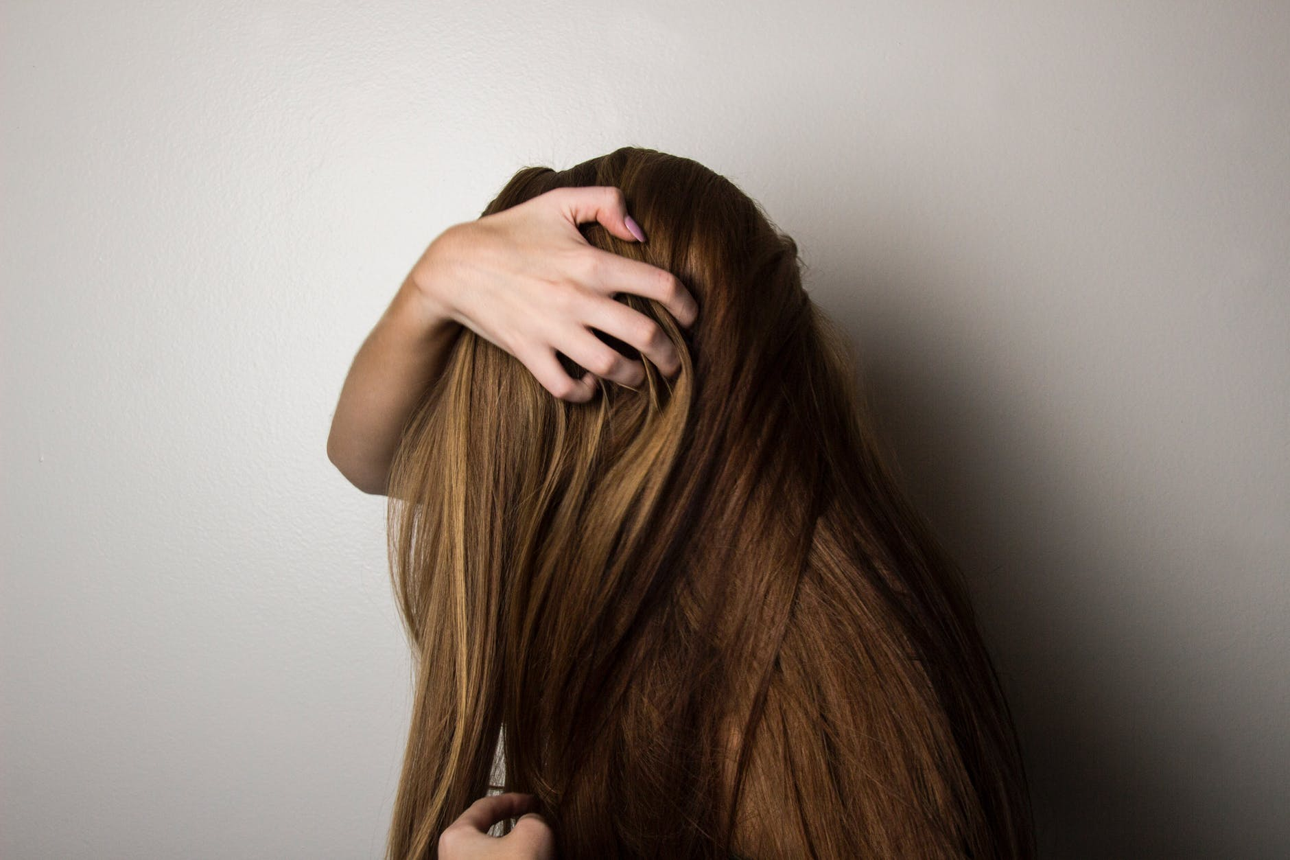 Brunette woman combing hair covering face with hand
