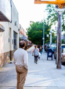 balding man on a suburban sidewalk