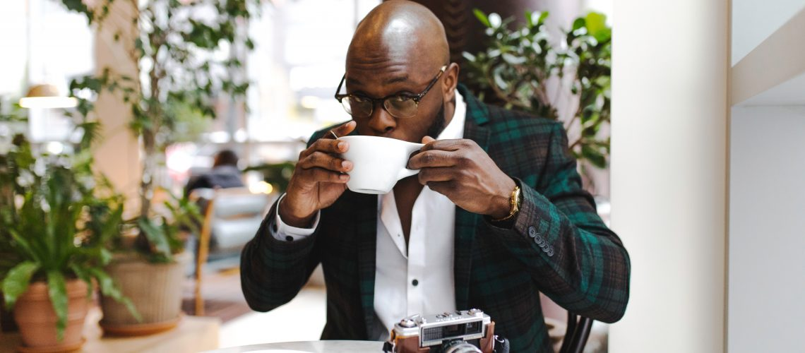 A bald celebrity drinking coffee