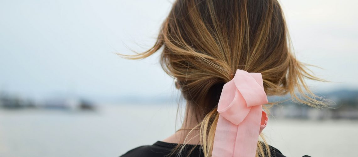 Lady with her hair tied back in a pink ribbon